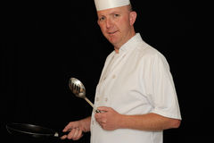 Chef with spoon. Chef in white uniform holding metal spoon and pan on black background Stock Image