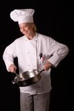 Chef Spoons from Frying Pan. Passive posed female Chef in uniform spooning from a skillet Royalty Free Stock Images