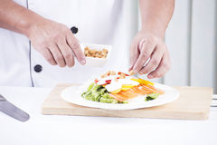 Chef sprinkle biscuits on Salad Royalty Free Stock Photography