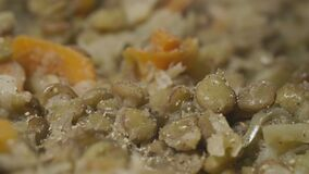 Chef sprinkle with spices lentils with carrots and onions using a spatula in a pan