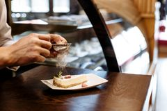 Chef sprinkled with powdered sugar sieve of a piece of cake on a plate on a wooden table royalty free stock images