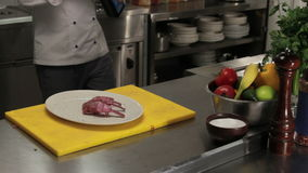 Chef sprinkling portion of ribs with spices, medium shot. Chef in restaurant sprinkling portion of ribs with salt and pepper, pouring oil to grill it, medium stock footage