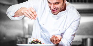 Chef sprinkling spices on dish. In commercial kitchen royalty free stock photography