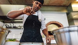 Chef sprinkling spices on dish in commercial kitchen. African male cook preparing food in restaurant kitchen, adding seasoning royalty free stock photography