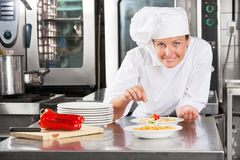 Chef Sprinkling Spices On Food. Portrait of female chef sprinkling spices on food at commercial kitchen counter Royalty Free Stock Photography