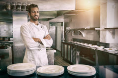 Chef standing with arms crossed behind counter in profesionnal kitchen. Portrait of smiling young chef standing with arms crossed behind counter in professional royalty free stock images