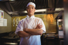 Chef standing with arms crossed in the commercial kitchen. Portrait of chef standing with arms crossed in the commercial kitchen stock photography