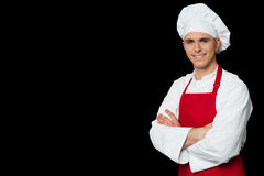 Chef standing with arms crossed. Confident male chef smiling and folded hands royalty free stock image