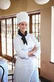 Chef standing with arms crossed. In a restaurant stock photography
