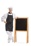 Chef standing by a blank blackboard. Full length portrait of a chef standing by a blank blackboard isolated on white background stock photography