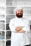 Chef standing in bright, spacious modern kitchen. Half length portrait of male chef cook with arms crossed standing in modern luxury kitchen royalty free stock photos
