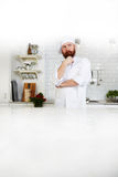 Chef standing in bright, spacious modern kitchen Royalty Free Stock Images