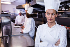 Chef standing in commercial kitchen in a restaurant. Chef standing in commercial kitchen and three chefs discussing In background royalty free stock photos