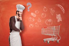 A chef standing half-turn and thinking about something with a supermarket trolley aside on terracotta background with stock photos