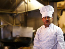 Chef Standing In Kitchen. Chef standing with blurred kitchen background Royalty Free Stock Image