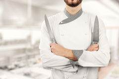 Chef standing in kitchen with knives in hands Royalty Free Stock Photography