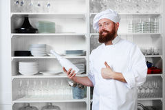 Chef standing next to shelves with dishes and holding a bottle of champagne for their visitors. Professional chef of luxury haute cuisine in white uniform and Stock Photography