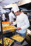 Chef standing at serving trays of pasta. In commercial kitchen stock photos