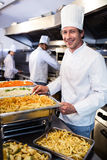 Chef standing at serving trays of pasta. Portrait of chef standing at serving trays of pasta in commercial kitchen stock photos