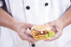 Chef stellte einen Burger dar Lizenzfreies Stockfoto