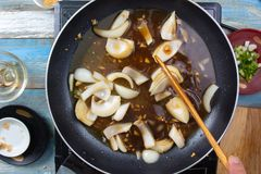 Chef stir fry onion in pan stock image