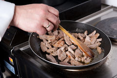 Chef stir meat. In frying pan Royalty Free Stock Photos