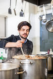 Chef stirring a huge pot of stew or casserole Royalty Free Stock Images