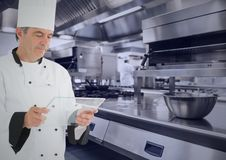 Chef with tablet in kitchen with blue overlay. Close-up of chef using virtual screen against digitally generated kitchen Stock Photos