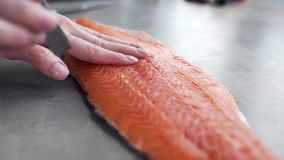 Chef takes out bones from the salmon fillet, cutting fish, dishes with fish, diet food, healthy cooking, at the kitchen. Chef takes out bones from the salmon stock video footage