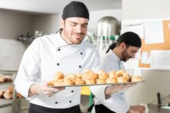 Chef Taking Aroma Of Freshly Baked Breads. Good looking baker smelling tasty chouxs in commercial kitchen royalty free stock photo
