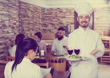 Chef taking care of adults at cafe table. Cheerful chef taking care of adults at cafe table Royalty Free Stock Photo
