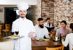 Chef taking care of adults at cafe table Stock Photos
