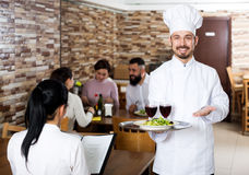Chef taking care of adults at cafe table Stock Photography