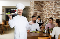 Chef taking care of adults at cafe table Royalty Free Stock Image