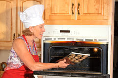 Chef Taking Cookies Out Of Oven Royalty Free Stock Image