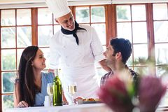 Chef talking to couple at restaurant. Male chef talking to couple at restaurant royalty free stock photo