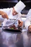 Chef tamisant le sucre glace au-dessus d'un dessert Photos libres de droits