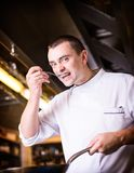 Chef is tasting the cooked dish stock photo
