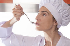 Chef tasting cream. Portrait of chef woman with professional jacket and hat tasting red sauce or cream puree like tomato ketchup in a steel soup spoon in her stock image