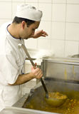 Chef tasting food. A chef working in an industrial kitchen, standing at large oven, holding large spoon with gulash Stock Photo