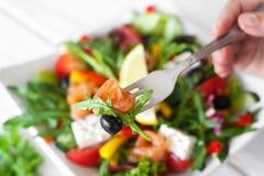 Chef tasting salmon salad with olives closeup Stock Photos