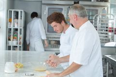 Chef teaching trainee how to become pastry chef royalty free stock images