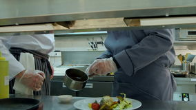 Chef teaching young trainee how to serve the sauce stock video footage