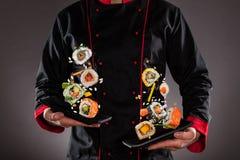 Chef tenant des plats avec des morceaux de sushi de vol photographie stock libre de droits