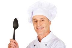 Chef tenant la cuillère en plastique noire Photographie stock