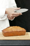 Chef Tests Knife Sharpness Over Banana Bread Royalty Free Stock Images