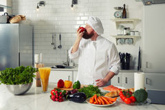 Chef with a thick beard enjoys the smell of fresh tomatoes Royalty Free Stock Photos