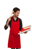 Chef thinking cookbook. A thinking chef reading in a cookbook scratching his head with a spoon Stock Image