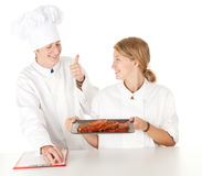 Chef with thumb up examining cook Stock Photos