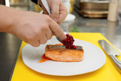 Chef is topping fried salmon steak with berry sauce Royalty Free Stock Images